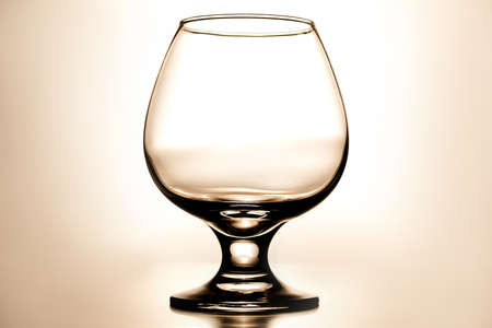 vertical photo empty clean transparent with glares glass for cognac on light beige background with gradient Foto de archivo