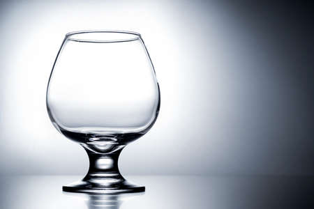 empty clean transparent with glares glass for cognac on gray white background with gradient Foto de archivo