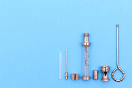 antique syringe disassembled into details on a blue background