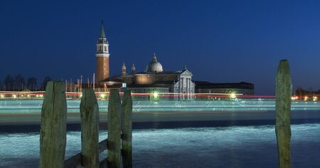 View on the island of San Giorgio in Venice in the winter night with the lights of passing ships traces photo