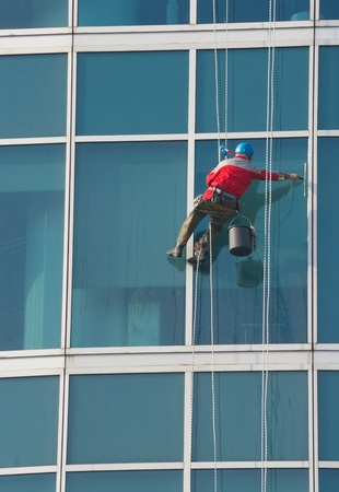 Climber - window cleaner perform the work at wall of an office building