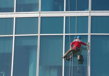 세탁기: 등산 - 창 청소기는 사무실 건물의 벽에 작업을 수행 스톡 사진