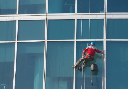 Climber - window cleaner perform the work at wall of an office building photo