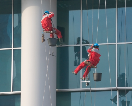 window washer: Climbers - window cleaners perform the work at wall of an office building Stock Photo