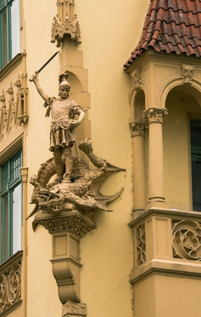 Sculpture of St  George on the front of the house in Prague photo