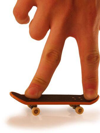 Riding on a miniature toy skateboard. On a white background. photo