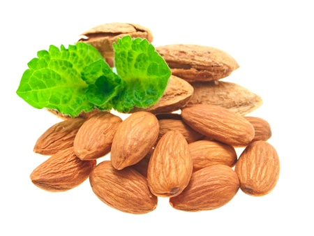 A pile of shelled and unshelled almonds, with a sprig of mint. On a white background. Stock Photo
