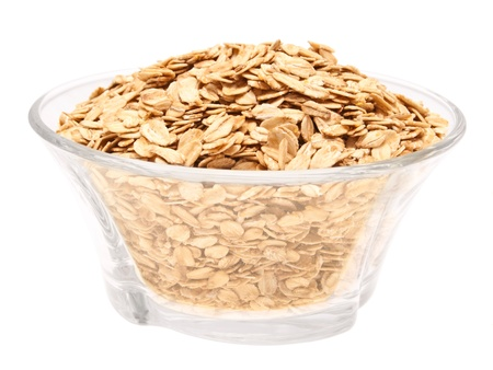 flakes: Rolled oats in a glass bowl - top view  On a white background