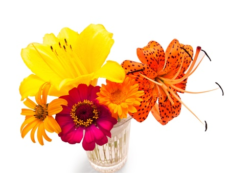A bouquet of flowers of yellow lilies, daisies, and the leopard lily, in a glass vase. Isolated on white. photo