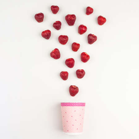 strawberries fall into a white pink paper cup on a white background Standard-Bild