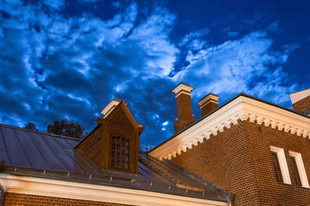 The roof of the house is made of red brick against the night sky, the moon shines through the clouds Stock Photo