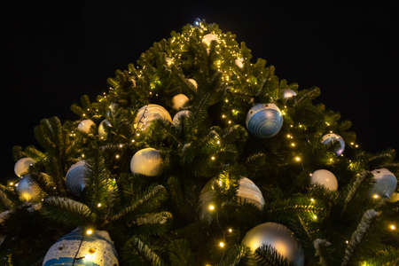 large Christmas tree with silver and blue balls against the black sky, view from below Imagens