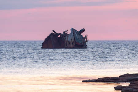 sunken rusty old ship at sunset, in the foreground rocks Zdjęcie Seryjne