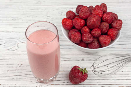 strawberry cocktail, blender and plate with strawberries on a white wooden background