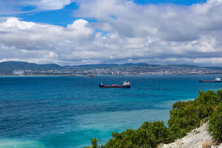 Blue sea with cargo ships against the blue cloudy sky, in the background of the city. View from the cliff Standard-Bild