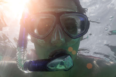 mans face in snorkeling under water, the sun shines from behind