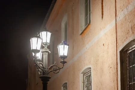 old street lamp shines at night against the backdrop of an old yellow building