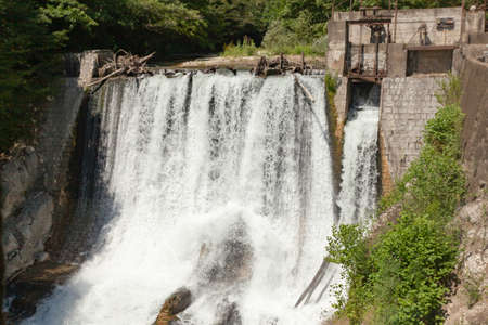 Old abandoned hydroelectric power plant against a backdrop of green trees