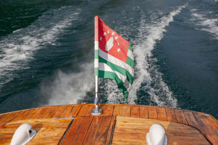 pleasure boat with Abkhazian flag floats on Lake Rizza, view from behind