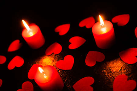 On a black textured background are scattered red hearts and stands three burning red candles, used as a background or texture