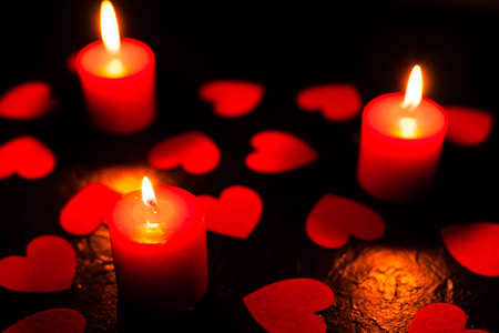 On a black textured background are scattered red hearts and stands three burning red candles, with blurry background, used as a background or texture, soft focus