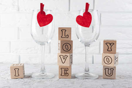 against the white brick wall two wine-empty glasses with red hearts and cubes with letters laid out the phrase I love you