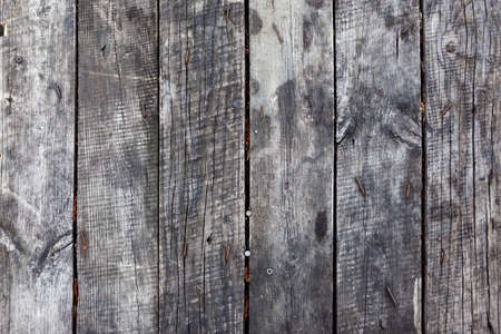 An old gray wooden close-up fence. Use as a background or texture