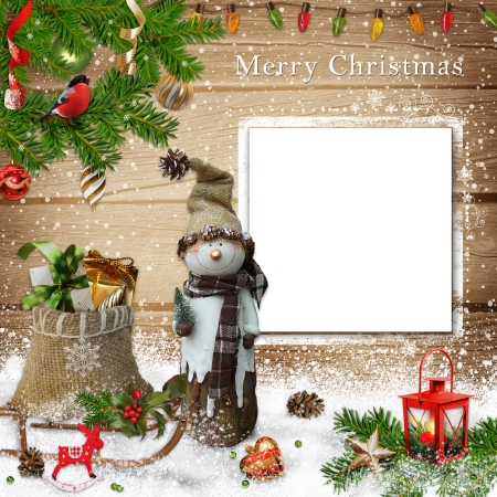 Christmas decoration with snowman, gift bag and a card on a wooden background photo
