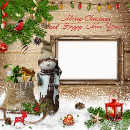 Christmas decoration with snowman, gift bag and the frame on a wooden background photo