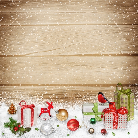 invitation card: Christmas decorations and gifts in the snow on a wooden background