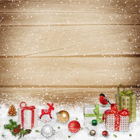ročník: Vánoční ozdoby a dárky ve sněhu na dřevěné pozadí Reklamní fotografie