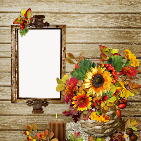 A bouquet of flowers, leaves and berries in a wicker vase, photo frame or text on the wooden background