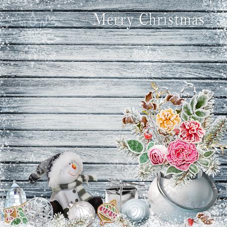 Natale sfondo con un mazzo di fiori con il gelo, il pupazzo di neve, ornamenti di Natale su una tavola di legno nevoso