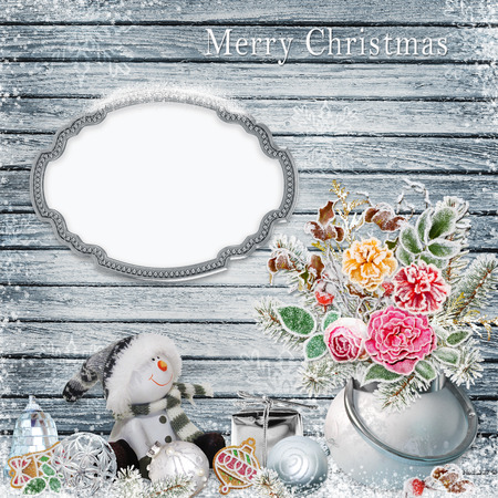 christmas decorations: Christmas background with a bunch of flowers with frost, snowman, frame for text or photos, Christmas decorations on a snowy wooden board