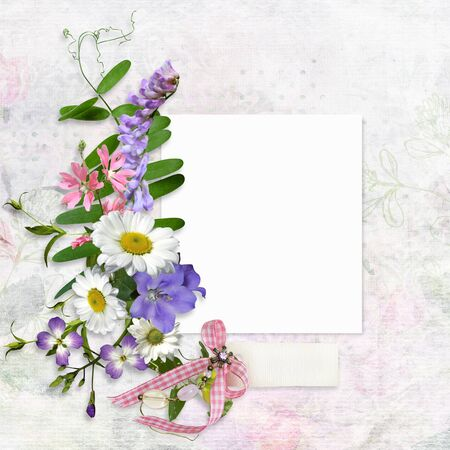 Vintage background with card for photo or text and a bouquet of summer meadow flowers