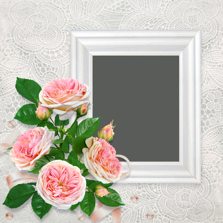 Frame with a bouquet of pink roses on a beautiful vintage lace background