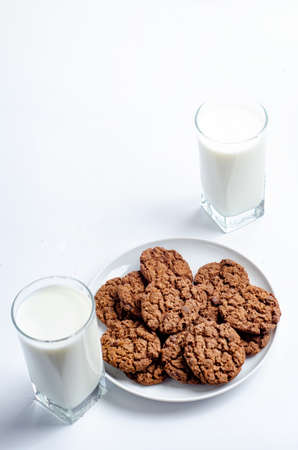 chocolate chip cookies and glass of milk on white background Foto de archivo