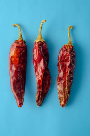 Dried red hot pepper with pastel blue background. Composition with copy space. Minimal natural luxury. Top view, flat lay. Banco de Imagens