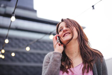 Beautiful young brunette woman in urban background talking on smartphone