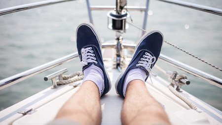 The legs of a man in sneakers sitting on the on the yacht in sea. Summer relaxation