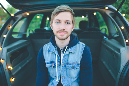 Portrait of happy young hipster man sitting besides his car on a summers day Imagens