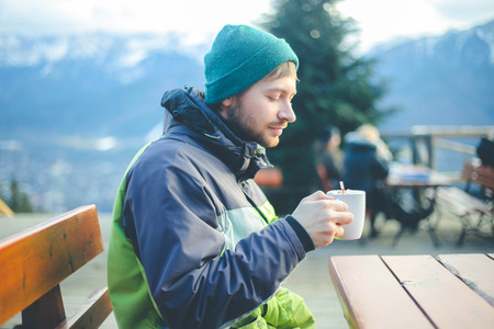 Man with cup of hot drink warms in winter mountains Imagens
