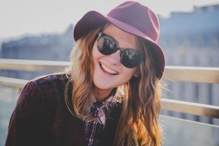 Lifestyle portrait of young cute hipster woman in a hat laughing on the street