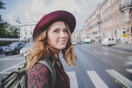 Lifestyle portrait of young cute hipster woman in a hat walking on the street Imagens