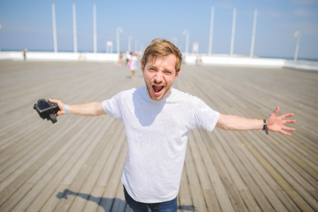 Young hipster man photographer posing and holding camera on a pier. Enjoying travel Imagens