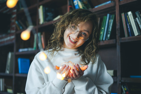 Portrait of young cute girl in glasses holding garlands of lights Imagens