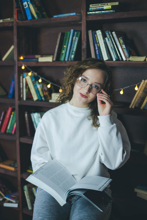 Portrait of a young student girl in glasses reading book at library