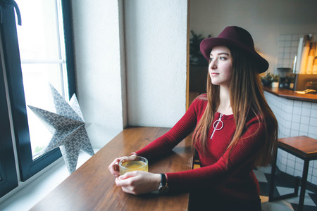 Beautiful young girl in hat with cup of tea looking at window in cafe