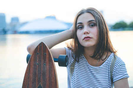 Portrait of young caucasian girl holding wooden longboard skateboard Imagens