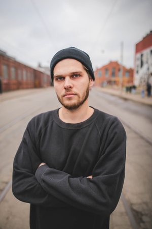 Portrait of young stylish hipster man in black hat in a urban background